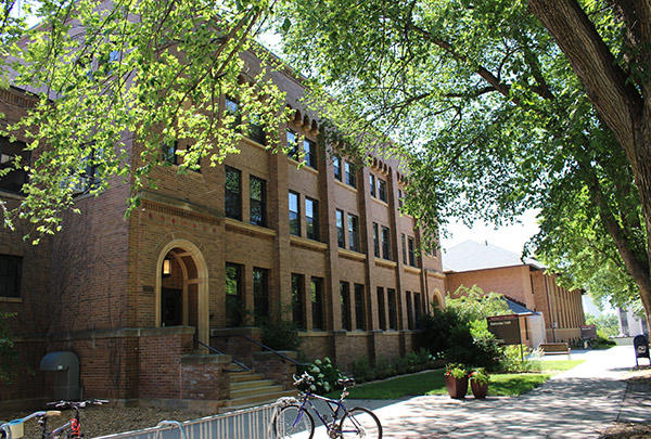 Behmler Hall, a Craftsman-style three-story red brick building, on a summer day